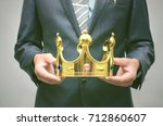 Small photo of VIP client. Premium user concept. Success. Business man in suit holding in hands golden crown. Top manager. Best employee of the year award.