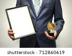 Small photo of Top manager award mockup. Best office employee award. Business man holding empty blank photo frame (gratitude letter) in one hand and gold medal in another one. Gratitude concept. Grateful letter.