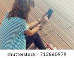 young woman using cellphone... | Shutterstock . vector #712860979