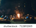 group of people near camp fire... | Shutterstock . vector #712892005