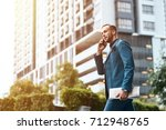 Small photo of Rapid tempo of life. Low angle of a self assertive handsome businessman talking on phone and holding a newspaper while walking along the street