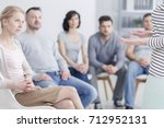 Small photo of Caucasian woman talking to group of people during sharing session