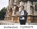 Small photo of Young and ambitious tourist is standing on the sidewalk near the cathedral and reading a map. The guy was lost but now he has finally found his current location. So that's why he is so happy.