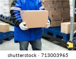 worker carrying a goods box in... | Shutterstock . vector #713003965