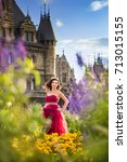 Small photo of A beautiful woman, a princess in a red lavish dress, is standing in a blooming garden. Ancient castle on the background.