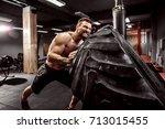 shirtless man flipping heavy... | Shutterstock . vector #713015455