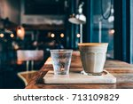 Small photo of Glass of latte pun on the wooden plate with cup of water in cafe background