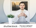 young man in shirt sits with... | Shutterstock . vector #713119507
