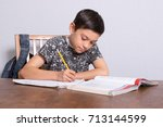 Young teenage boy doing his homework - stock photo