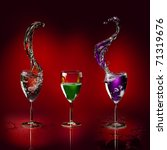 three glasses with colored liquid splashing on a deep red background - stock photo