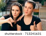 Small photo of Funny Girls with Thumbs up and Thumbs Down Rating Different The Same Situation - Portrait of two young women with opposite opinions expressing it with funny gestures