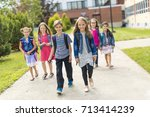 Small photo of Great Portrait Of School Pupil Outside Classroom Carrying Bags