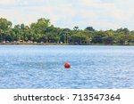 red buoy on big lake in city in ...   Shutterstock . vector #713547364