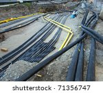 Messy building site with cables and pipes - stock photo