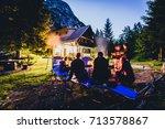 friends sitting around bonfire... | Shutterstock . vector #713578867