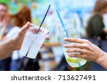Small photo of Drinking lemonade cocktail glasses with straw and ice shaking, man and woman friend hands cheers at an event with blurred red hair people and colored wall background