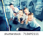 Small photo of Positive family of five is using PC in time having fun together in lost labroom.