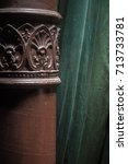 Small photo of Ornate acanthus decoration on a brown painted cast iron pole in a room interior in front of a green drape or curtain
