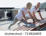 upbeat couple doing stretching... | Shutterstock . vector #713826805