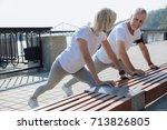 Stock photo upbeat couple doing stretching exercises together 713826805