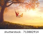 happy child girl on swing in... | Shutterstock . vector #713882914