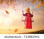 happy child on swing in sunset... | Shutterstock . vector #713882941