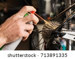 Small photo of Closeup of male hands cleaning and oiling a bicycle chain and gear with oil spray. Working process