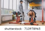 Small photo of Young fitness woman exercising abdominal in the gym - muscular man looking to her