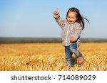 happy 2 year old girl walking... | Shutterstock . vector #714089029
