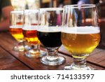 a flight of four beers on an... | Shutterstock . vector #714133597