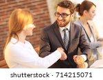 friendly handshake between... | Shutterstock . vector #714215071