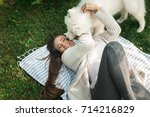 young woman resting with a dog... | Shutterstock . vector #714216829