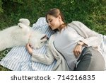young woman resting with a dog... | Shutterstock . vector #714216835