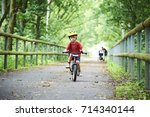 child boy on a bicycle on... | Shutterstock . vector #714340144