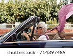 old woman driving a convertible ... | Shutterstock . vector #714397489