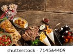 wooden table full of grilled... | Shutterstock . vector #714564409