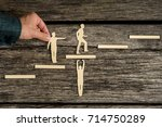 Small photo of Teamwork concept on rustic wood with group of silhouette cutouts and a male hand helping a paper cutout of a climbing man.