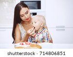 the mother feeds the child's... | Shutterstock . vector #714806851