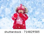 baby playing with snow in... | Shutterstock . vector #714829585