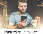 young bearded hipster man sits... | Shutterstock . vector #714913591