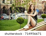 a young girl sits on a bench in ... | Shutterstock . vector #714956671