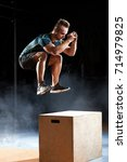 Small photo of Box jump exercise young man doing functional workout at the gym