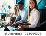three young smiling colleagues... | Shutterstock . vector #715044379
