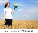 Young Businesswomen in white keeping globe in hand at wheat field - stock photo