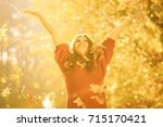 girl tossing up leaves. young... | Shutterstock . vector #715170421