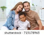 Small photo of Happy couple with adopted African-American boy at home