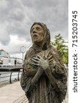 Small photo of Dublin, Ireland - August 7, 2017: Great Irish Famine bronze statue set on Custom House Quay along Liffey River in Docklands. One slender female figure. Green trees.