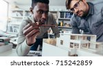 two male architects in office... | Shutterstock . vector #715242859