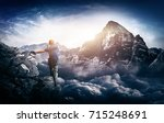 Stock photo a mountain climber with a majestic sunrise view over towering snow capped mountains and cloud tops 715248691