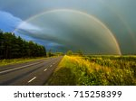 rainbow and dramatic sky over... | Shutterstock . vector #715258399